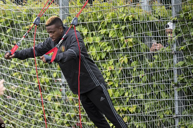 Liverpool striker Divock Origi stretches his upper body and core as the Belgium players prepare for Friday