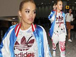 21 June 2016. Rita Ora arriving back in England for the first time in months, on a flight from New York. Rita told snappers she had missed them, and was wearing one of the latest Adidas tracksuits that she has designed, with a typically bright and bold pattern. Her sister Elena joined her on the flight home. Credit: Will/GoffPhotos.com   Ref: KGC-305