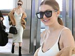 06/20/2016\nModel, Gigi Hadid is all smiles as she catches a departing flight at Pearson International Airport in Toronto, Canada. The American fashion model appeared to be in great spirits as she made her way through the International terminal this morning. The 21 year old was spotted in a low cut cleavage bearing dress while graciously taking the time to greet fans before catching her flight.\n Please byline:TheImageDirect.com