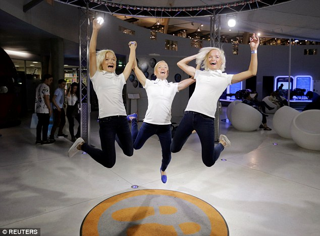 Estonia's Olympic team female marathon runners triplets (L-R) Leila, Lily and Liina Luik play with a tech installation after a training session