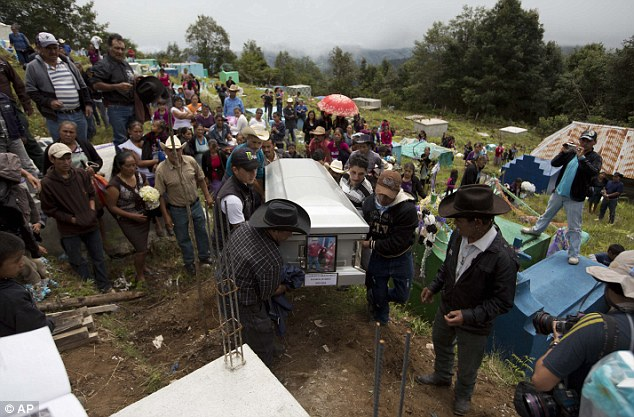 Relatives arrive at the local cemetery carrying the coffin containing the remains of Gilberto Francisco Ramos Juarez