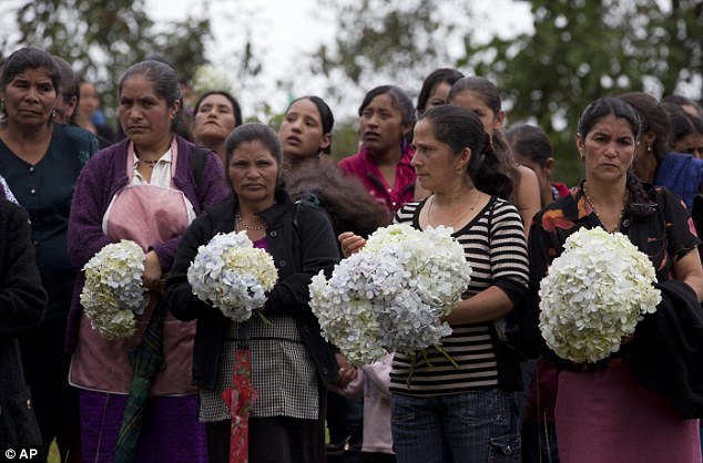 Neighbors hold bouquets of Hydrangeas during the burial service of Gilberto Francisco Ramos Juarez, a Guatemalan boy whose decomposed body was found in the Rio Grande Valley of South Texas