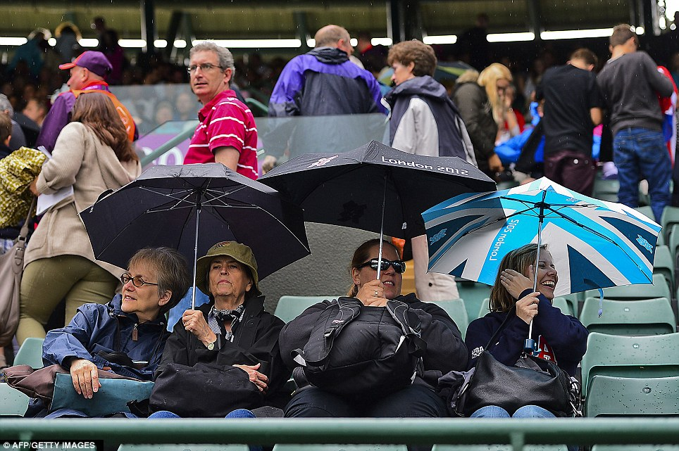 A very British summer: Spectators shelter from the rain under their umbrellas before men's single tennis first round in Wimbledon