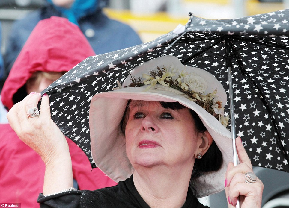A spectator shelters from the rain during the dressage equestrian event in Greenwich Park