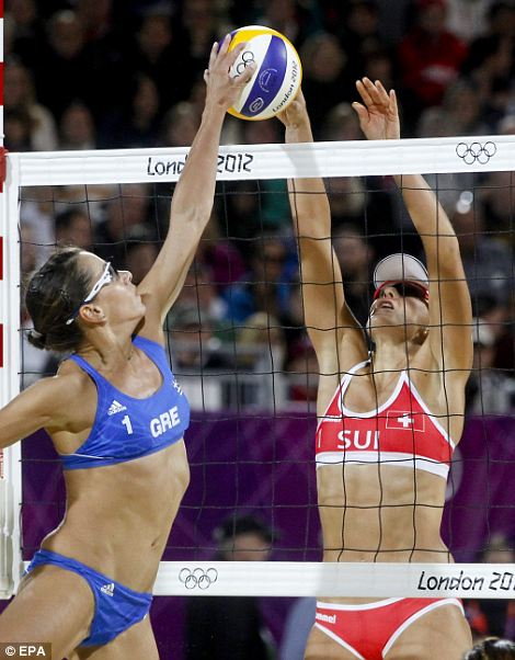 Greece's Maria Tsiartsiani, in blue, and opponent Simone Kuhn of Switzerland compete for the ball