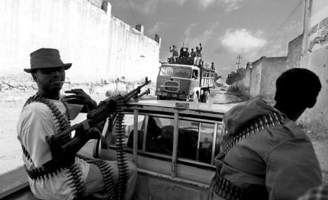 Gunmen cruise the streets in their  'Technical' , a converted pick-up truck with a heavy machine gun mounted on its back
