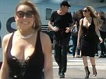 Mariah Carey and James Packer arriving at London Heliport.   See SWNS story SWMARIAH; Windswept Mariah Carey shows off her curves in a racy black dress as she steps off a helicopter after touching down in the UK. The sultry songbird was snapped with arms wrapped around billionaire beau James Packer, 48, as they arrived at London Heliport on Sunday.Wearing a figure-hugging black dress and glam gladiator stilettos, stunning Mariah, 46, looked loved up.