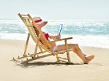 A young unidentifiable Asian woman sitting on a bamboo beach chair and reading an eBook tablet computer, relaxing on vacation in the tropical paradise of Kauai, Hawaii, USA. She wears a sun hat and bikini, sunbathing and looking at a view of a horizontal Pacific Ocean seascape. Blue sky and white sand provide copy space.