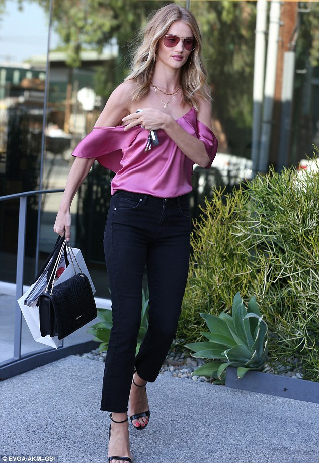Dowtown girl: Rosie showed off her toned arms  in a rose-coloured, satin top with draped sleeves