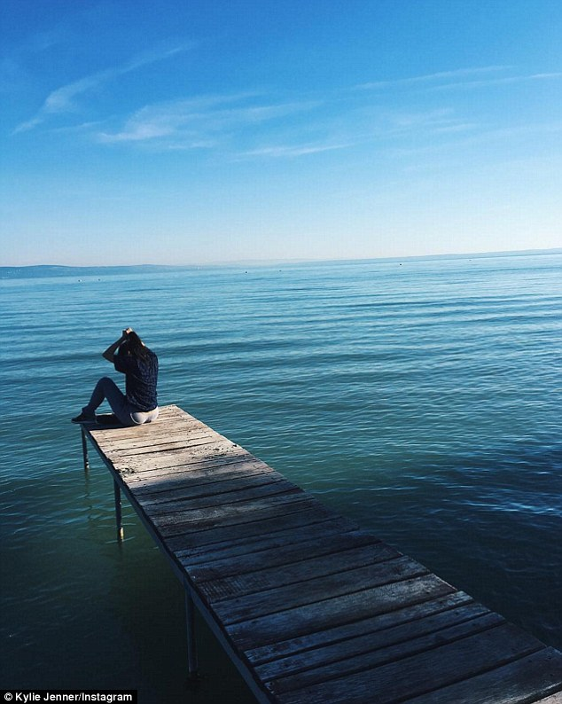 Peace and quiet: Jenner Instagrammed a snap of herself playing with her ponytail as she sat at the edge of a dock during her travels