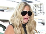 Tuesday, July 26, 2016 - Kim Zolciak arrives at LAX holding onto a plastic Solo cup and showing extremely plump lips after SnapChatting a trip to her plastic surgeon yesterday. The reality TV star lookis sexy in a sheer black bodycon top, leggings and heels as she leaves L.A. with NFL hubby Kroy Biermann and children Brielle and Ariana and Kroy Biermann Jr. Gio/X17online.com