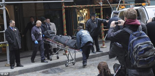 Tragedy: Officials carry the body of Mark Madoff out of his New York apartment today after he was found hanged