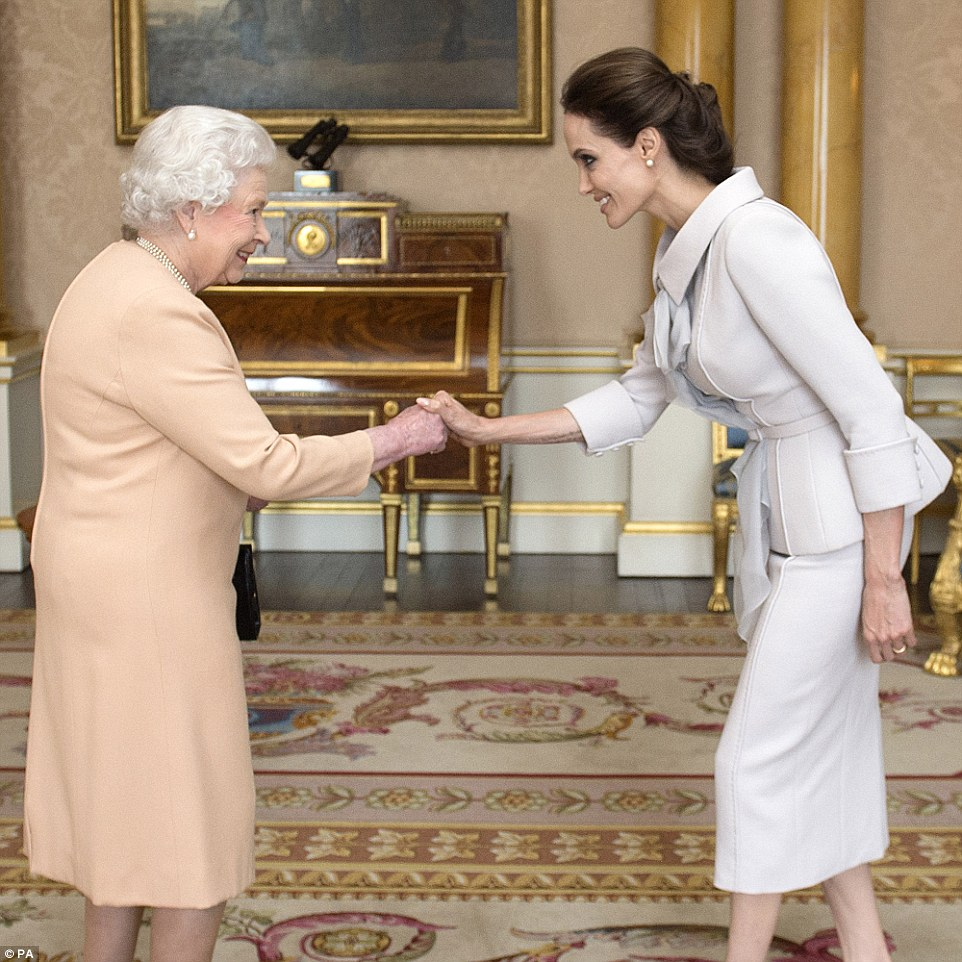 Celebrity guest: Actress Angelina Jolie is pictured being presented with the Insignia of an Honorary Dame Commander of the Most Distinguished Order of St Michael and St George by Queen Elizabeth II in the 1844 Room at Buckingham Palace on October 10, 2014