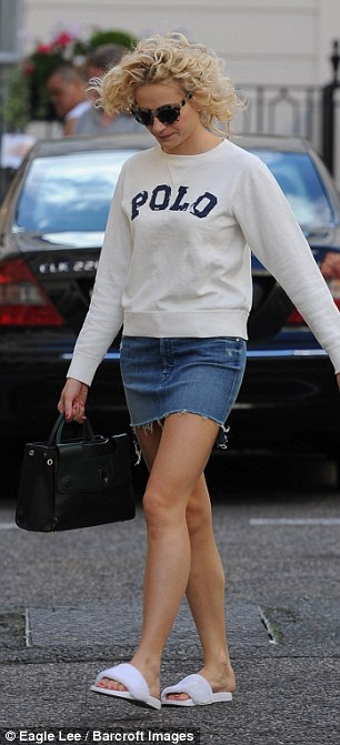 Sporty: She covered up in a sporty Polo sweatshirt in a cream shade, teamed with a denim mini skirt which flaunted her toned and tanned legs