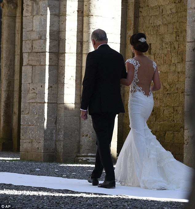 Elegant: The bride, accompanied by her suited father, looked stunning in an ivory gown featuring a low-cut back framed by lace embroidery