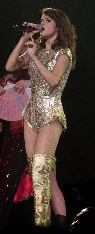 Metallic magic: She also sported a gold cap-sleeved one-piece with a pair of matching boots
