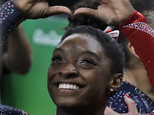 United States' Simone Biles forms a heart shape with her hands at the end of the artistic gymnastics women's qualification at the 2016 Summer Olympics in Rio de Janeiro, Brazil, Sunday, Aug. 7, 2016. (AP Photo/Rebecca Blackwell)