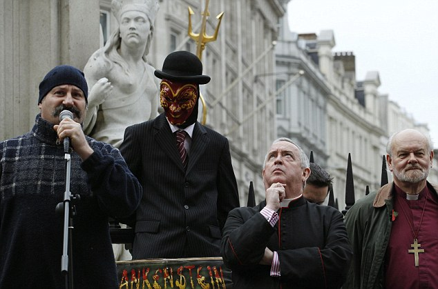 An unlikely crowd: A demonstrator directs questions to Rt Rev Knowles (second from right), and the Bishop of London, Richard Chartres (right) at the weekend