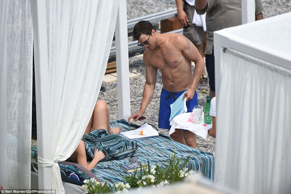 Line practise? Jamie appeared to clutch his script as he joined Dakota by the sun beds