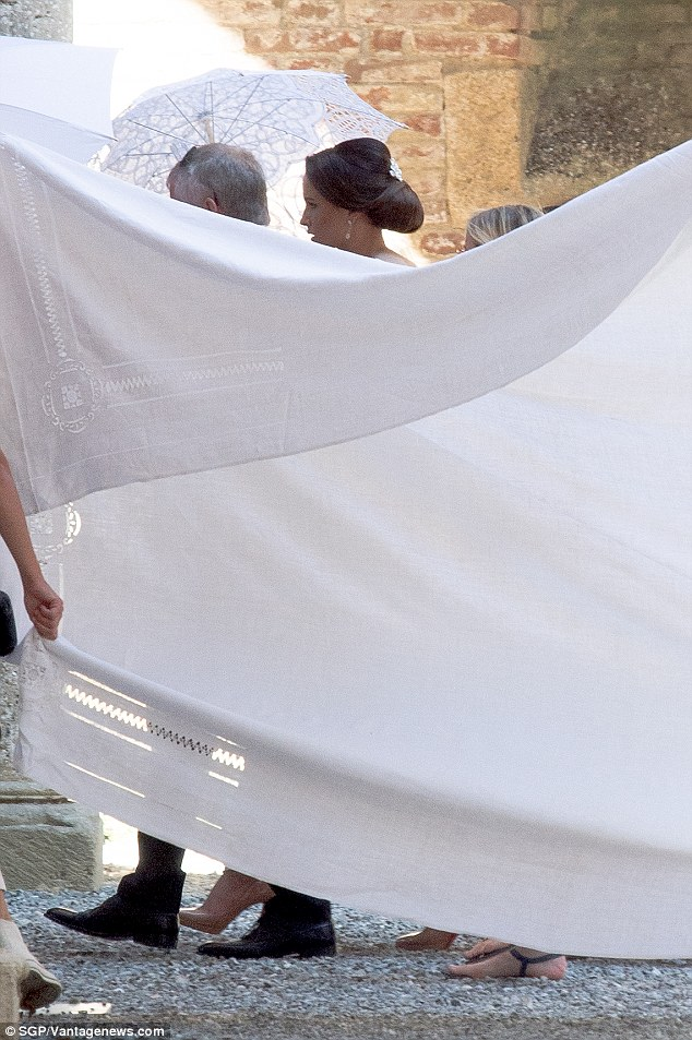 Cover (up) girl: The bride was protected by a white sheet, to protect a magazine deal, as she made her way into the ceremony