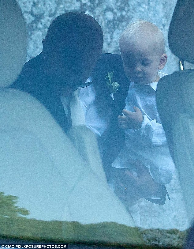 Ever the doting dad: Kimi looked stylish in a sharp navy suit and crisp white shirt, carrying their 19-month old son as he left the venue