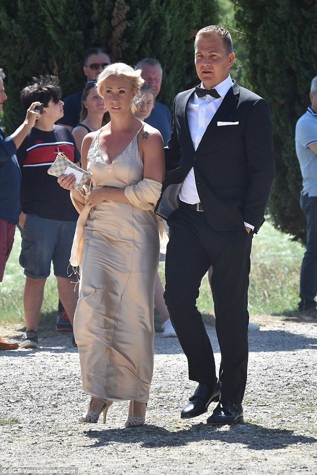 Golden girl: Another reveller looked sensational in a golden gown on the arm of a dapper gent