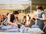 """This July 24, 2016 photo provided by Niels Alpert, Amanda Friedland, left, surrounded by friends and family adjusts her friend Betsy Davis's sash as she lays on a bed during her """"Right To Die Party"""" in Ojai, Calif. In early July, Davis emailed her closest friends and family to invite them to a two-day celebration, telling them: """"These circumstances are unlike any party you have attended before, requiring emotional stamina, centeredness, and openness. And one rule: No crying."""" The 41-year-old woman diagnosed with ALS,  held the party to say goodbye before becoming one of the first California residents to take life-ending drugs under a new law that gave such an option to the terminally ill. (Niels Alpert via AP)"""