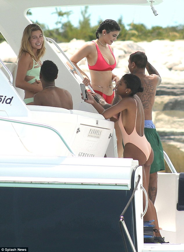 Just hanging: Kylie poured her curves into a bright red bikini as she enjoyed time on a luxury yacht with her friends