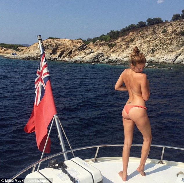 Cheeky! Millie went topless as she posed in a pair of red bikini bottoms as the loved-up couple enjoyed a day at sea earlier in the week