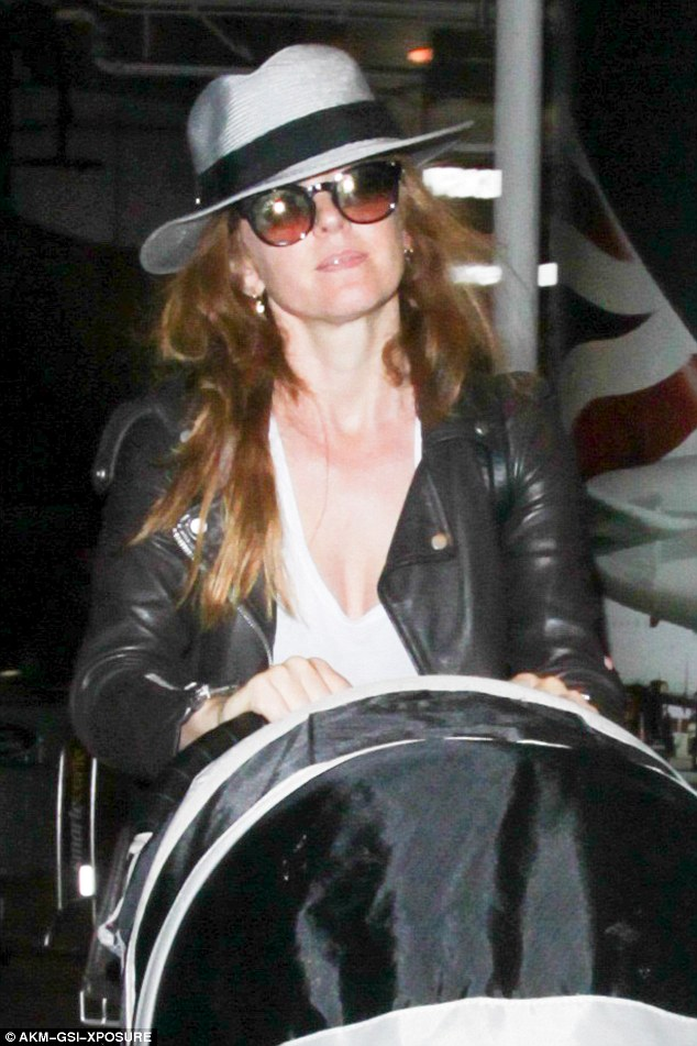 Summer style:Isla rocked a wide-brimmed hat and shades for the airport dash, while keeping her outfit casual with a fitted leather jacket teamed with baggy jeans