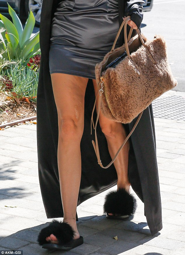 Furry accents! She topped the bedtime look off with a pair of fuzzy black slippers and a soft tan purse