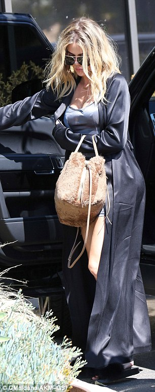 Bed head! Khloe's blonde disheveled locks were haphazardly styled in waves which cascaded past her silk-clad shoulders