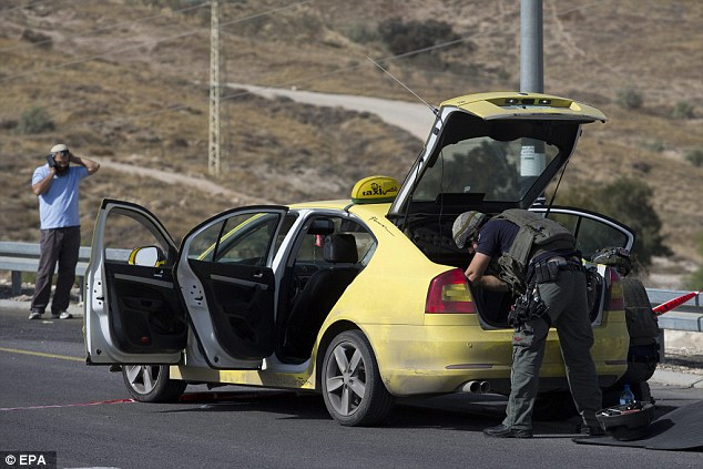 Israeli police search the taxi after the Palestinian man tried to run over people while at the wheel
