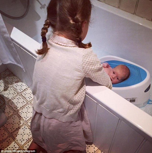 Proud mummy: Jools Oliver, 41, shared another adorable snap of her newborn son River Rocket, three weeks as he was bathed by the couple's youngest daughter, Petal Blossom, six