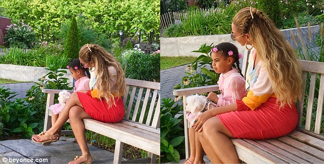 Doting: Beyoncélooked on as Blue Ivy doted on the family's dog, who was cuddled up in her lap