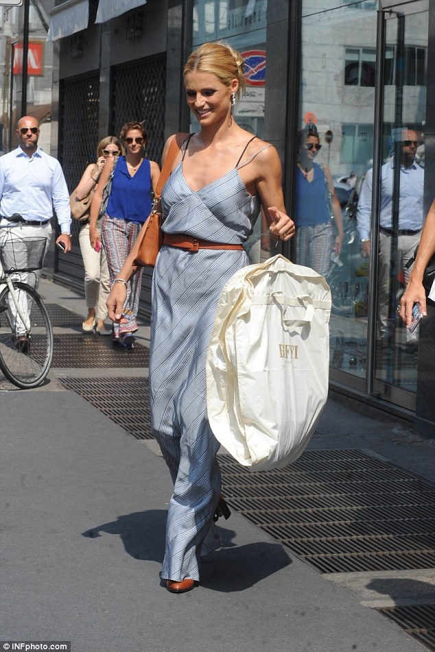 Quick change: She carried her dress as she walzed through Milan earlier that day