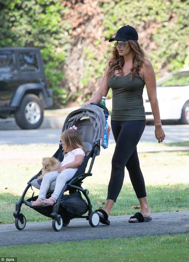 Glam mum: Tamara looked incredible as ever during her outing, opting for a casual look in figure-hugging leggings, a khaki vest top and black sliders