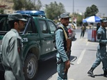 Afghan policemen stand guard at a checkpoint in Kabul on August 11, 2015