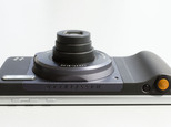 Motorola's Moto Z phone, with the Hasselblad True Zoom attachment, is viewed from the top side, Wednesday, Aug. 31, 2016, in New York. The orange camera shutter button is at right. Motorola says the attachment will appeal mostly to photography aficionados, but the company believes that's a sizable market. (AP Photo/Mark Lennihan)