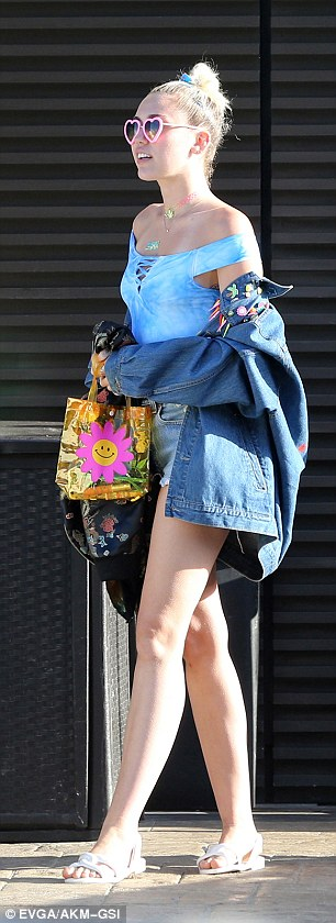 Leggy blonde: Mileydonned a sky blue off-the-shoulder top and barely there cutoffs which showcased her slender stems