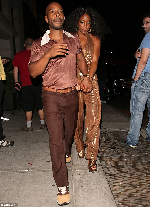Glamorous pair:Kelly's husband Tim Witherspoon didn't let down his lady in the fashion stakes, sporting brown nylon trousers, a wide collared retro top and caramel toned trainers