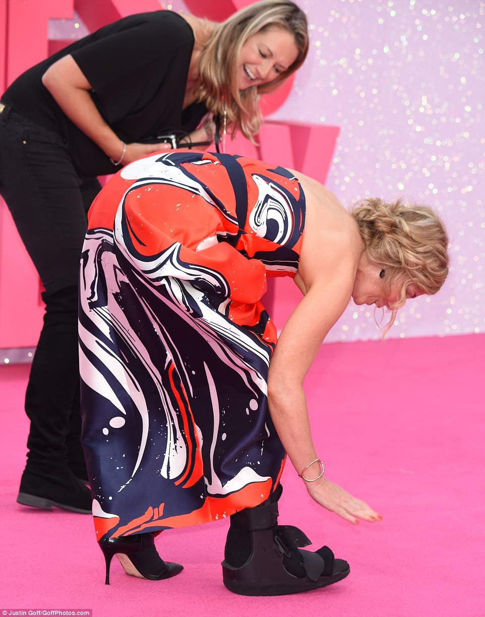 helping hand: An assistant was close by as Sally gingerly adjusted her leg brace on the pink carpet