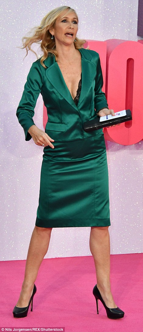 Jewel: She wore an emerald green satin suit over a plunging lace bodysuit as she arrived