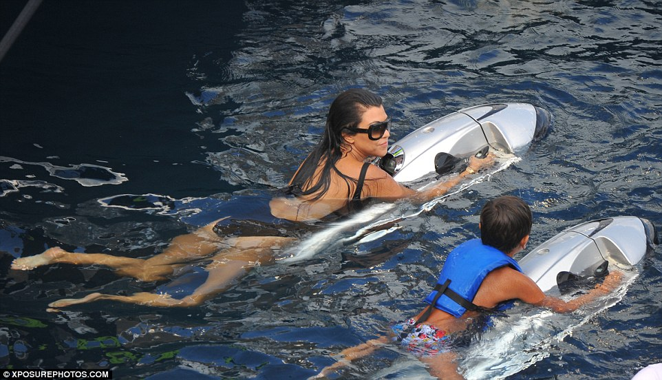 Side by side: Kourtney kept an eye on Mason as they played in the water on Monday
