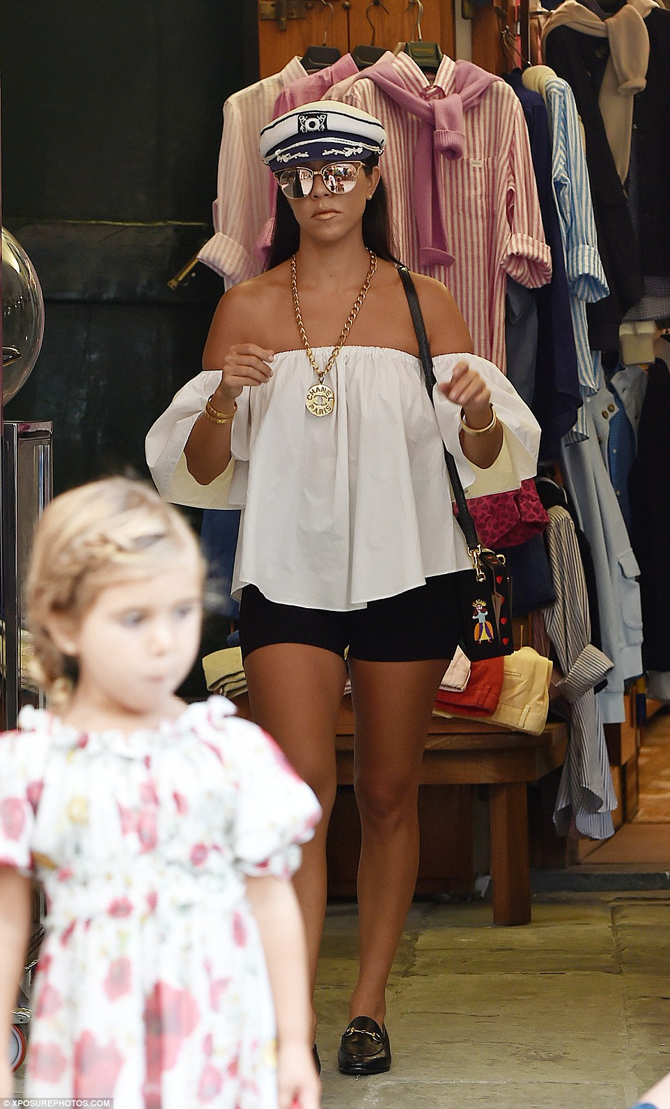 Off-the-shoulder: Kourtney paired her flowing top with tight black bike shorts