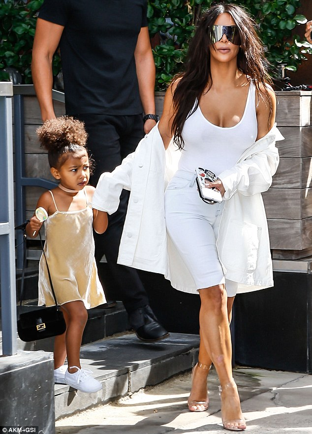 Help from the glam squad: Kim's tresses usually look oh so thick, bouncy and picture perfect. She is pictured here with three-year-old daughter North on Friday