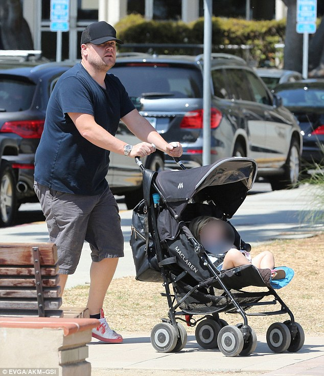 Going incognito: He wore a black baseball cap and simple white trainers as he pushed his one-year-old daughter along