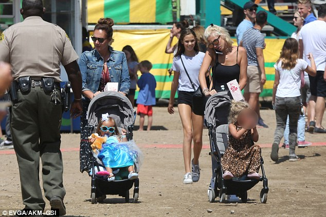 They see you strolling: Heading out to enjoy and all-American day of fun in the famous coastal region of LA, the two sisters treated their little girls to a day at the fair