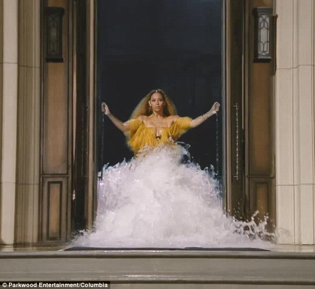 Enter the queen: Segueing into the song, she opens the doors wearing the exquisite layered yellow dress as the waters gushes out behind her.