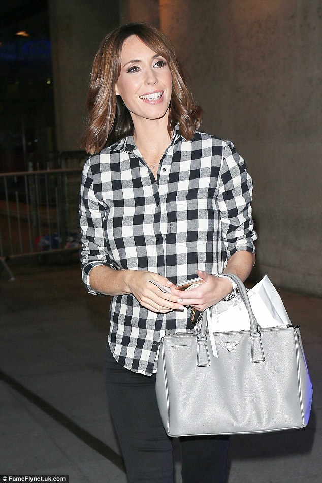 What are you hiding?The 39-year-old beamed as she tried to disguise her blossoming baby bump under a loose check shirt